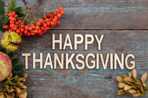 Feliz día de acción de gracias - texto con fondo otoñal de hojas caídas y frutas con lugar vintage en mesa de madera vieja.