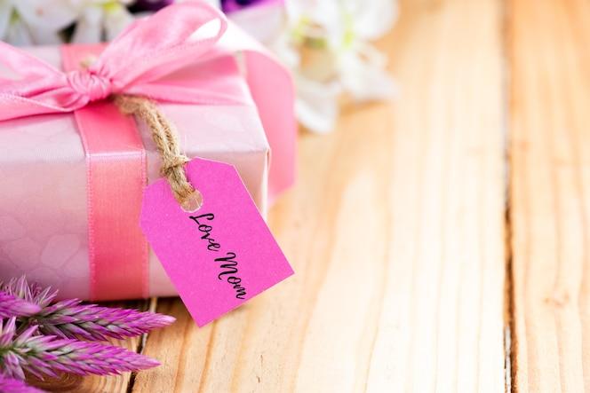 Feliz día de la madre concepto. caja de regalo con flor, etiqueta de madera en la mesa de madera.
