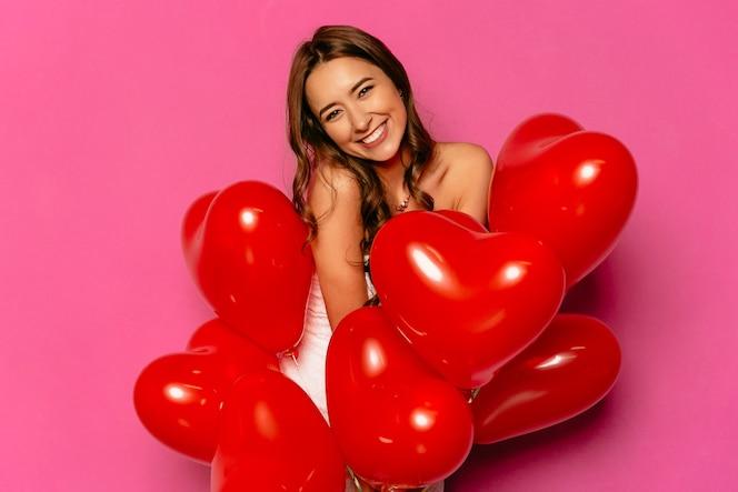 Feliz día de san valentín. atractiva mujer tímida, sonriendo ampliamente