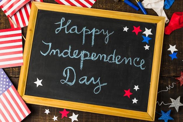 Feliz día de la independencia escrito en la pizarra decorada con la bandera de estados unidos; globos y estrellas en mesa