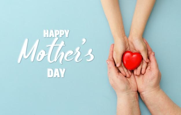 Feliz día de la madre corazón en manos de la hija y la madre sobre un fondo azul.
