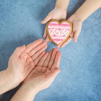 Feliz día de la madre corazón en las manos de mi hija y mi madre sobre un fondo azul.