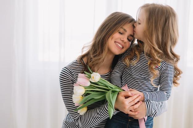 Feliz día de la madre. hija hija felicita a las mamás y le regala flores a sus tulipanes.