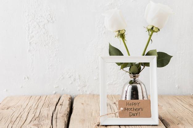 Feliz día de la madre inscripción con rosas blancas en florero.