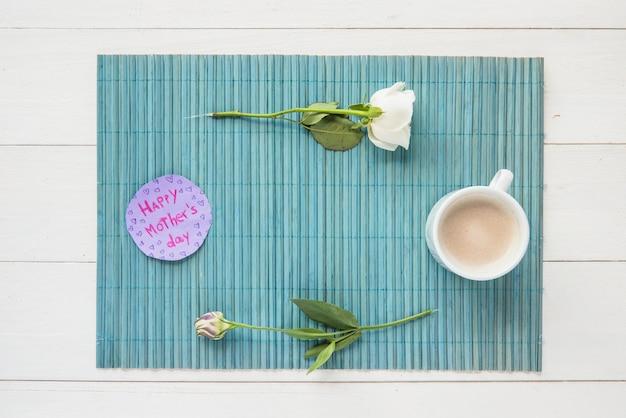 Feliz día de la madre inscripción con rosas y taza de café.