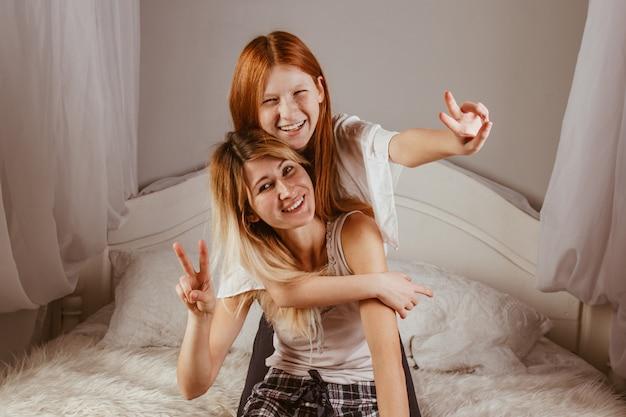 Feliz día de la madre. mamá y su hija están jugando a niña, sonriendo y abrazándose en la cama. vacaciones familiares y convivencia.