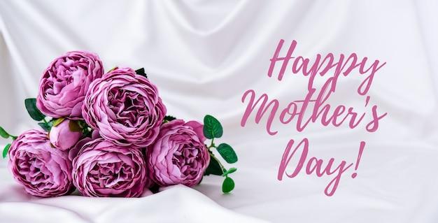 Feliz día de la madre tarjeta de felicitación de letras. ramo de peonías violetas. pastel claro brillante