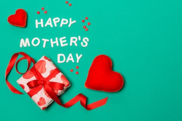 Feliz día de la madre título cerca de corazones y caja de regalo