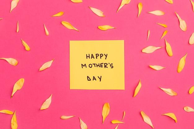 Feliz día de la madre título en papel entre pétalos de flores.