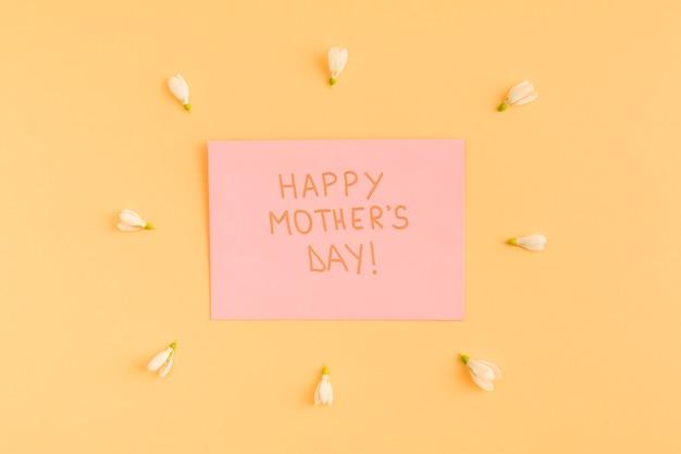 Feliz dia de las madres felicitaciones en papel entre flores.