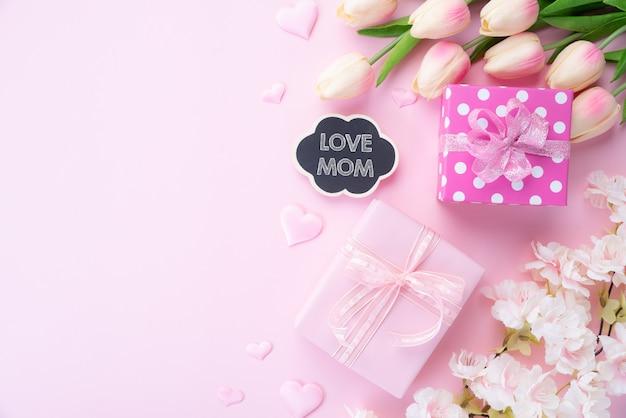 Feliz dia de las madres con regalo y flor rosa.