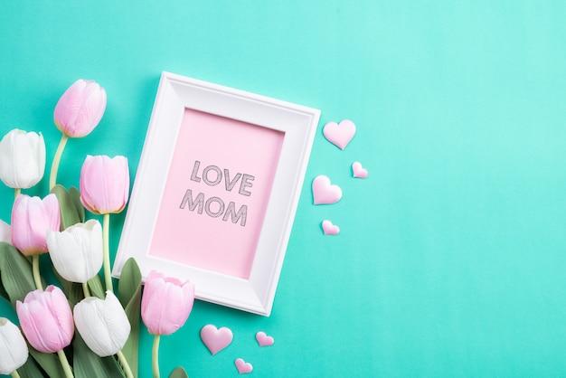 Feliz día de las madres en vista superior de flores de tulipán rosa y marco de fotos
