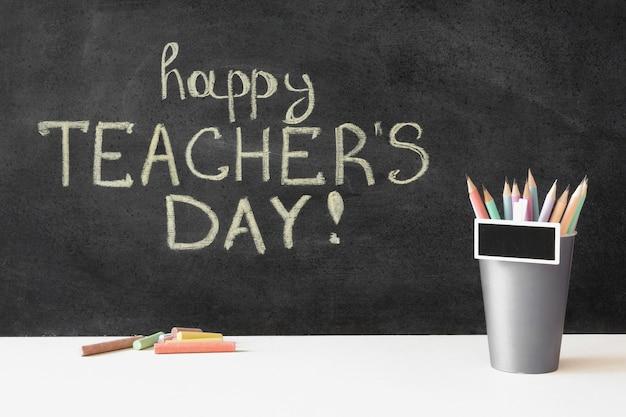 Feliz día del maestro en pizarra y lápices.