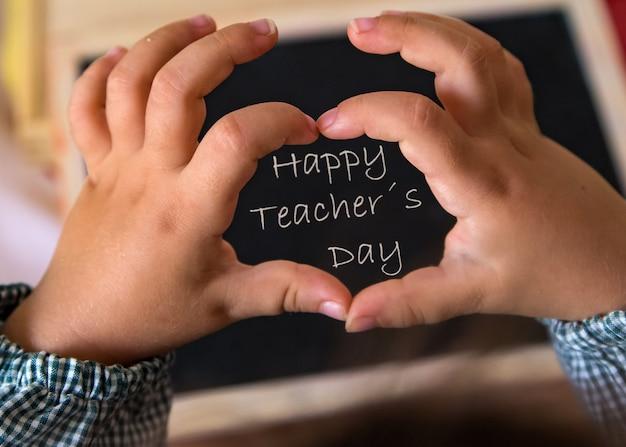 Feliz día de los maestros escrito en la pizarra con la mano de los estudiantes haciendo un corazón
