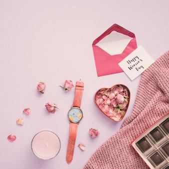 Feliz día de la mujer inscripción con pétalos de rosa y reloj.