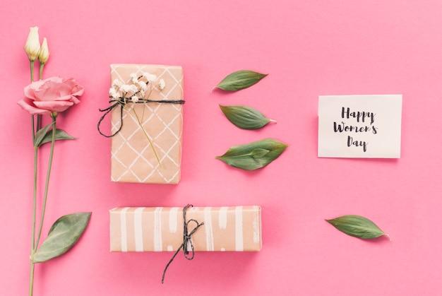 Feliz día de la mujer inscripción con regalos y flores.