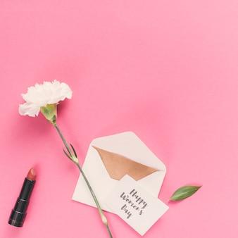 Feliz día de la mujer inscripción con sobre y flor en mesa rosa