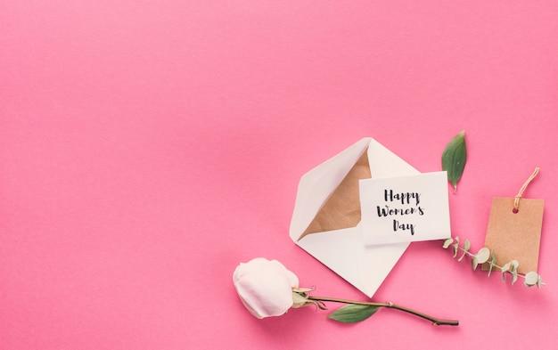 Feliz día de la mujer inscripción con sobre y flor en mesa