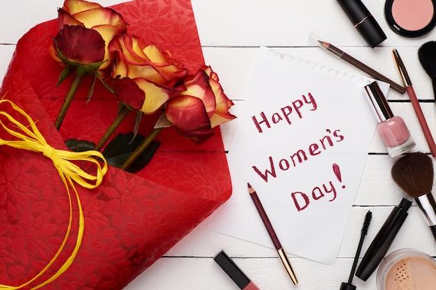 Feliz día de la mujer plana con rosas, tarjetas y productos de maquillaje, cosméticos.