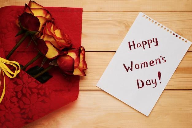 Feliz día de la mujer plana yacía con rosas en madera