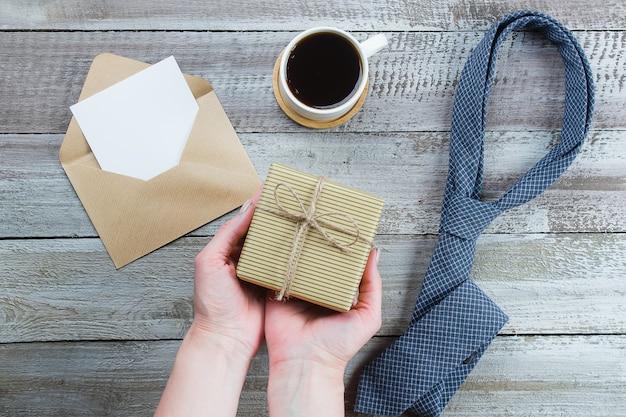 Feliz día del padre. manos de mujer con caja de regalo o presente. corbata azul, taza de café y vacía en blanco.