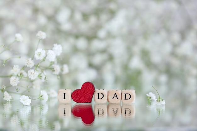 Feliz día del padre. texto i love dad sobre fondo con desenfoque de flores de gypsophila. tarjeta de felicitación por concepto de vacaciones.