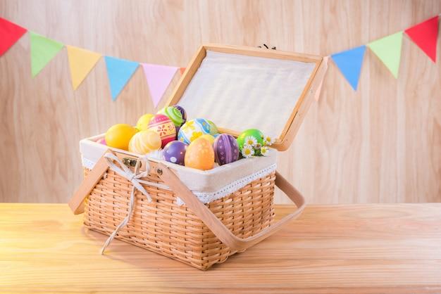 Feliz día de pascua coloridos huevos en la canasta en el piso de madera tienen celebrar banderas de fiesta