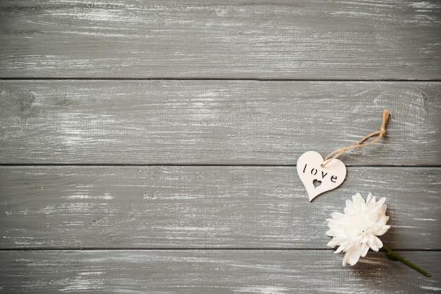 Feliz día de san valentín de fondo. corazón de madera blanco decorativo en gris rústico, con flores, concepto de san valentín.