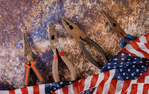 Feliz día del trabajo bandera americana y alicates herramientas.