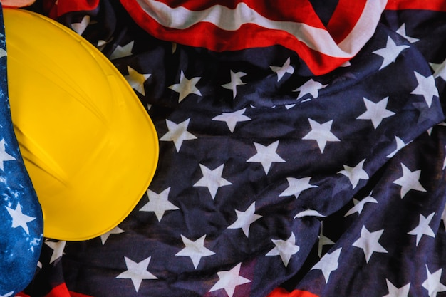 Feliz día del trabajo con la bandera estadounidense patriótica de ee. uu. y casco amarillo