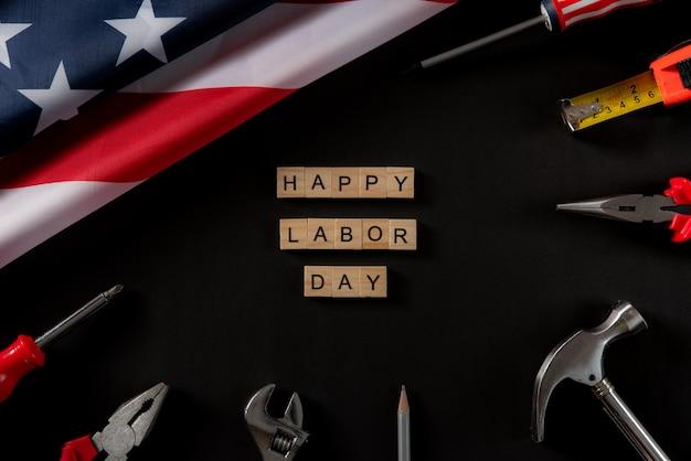 Feliz día del trabajo texto de madera y bandera estadounidense en la oscuridad
