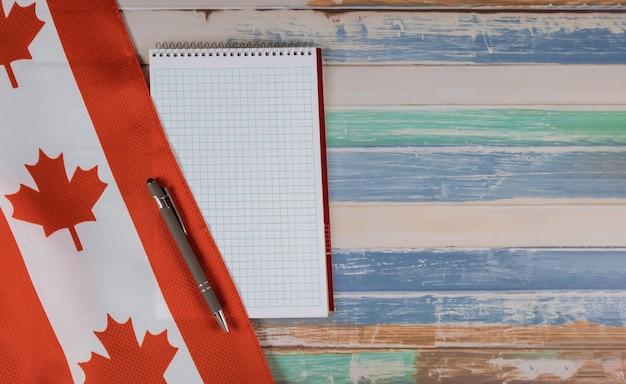 Feliz día de victoria banderas canadienses bloc de notas con pluma fondo rústico