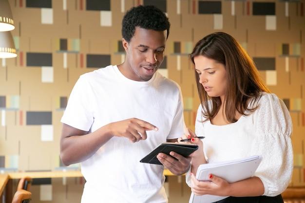Feliz diseñador afroamericano presentando proyecto al cliente en tableta y sonriendo