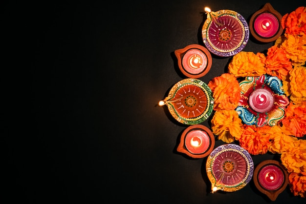 Feliz diwali-festival hindú, colorida lámpara de aceite tradicional diya en negro