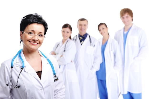 Feliz doctora riendo en primer plano y otros médicos