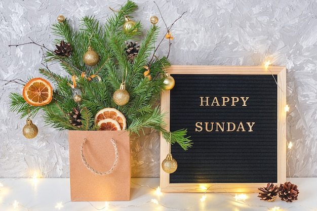 Feliz domingo texto en pizarra negra y festivo ramo de ramas de abeto con decoración navideña