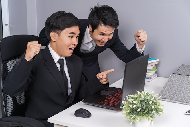 Feliz dos hombre de negocios usando laptop para proyecto de trabajo exitoso