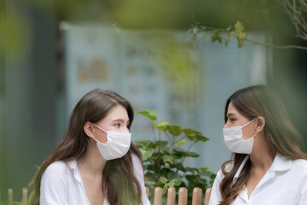 Feliz dos mujer joven con cara sonriente vistiendo mascarilla protectora hablando y riendo con centro comercial de comunicación