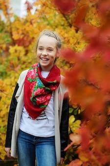 Feliz dulce niña preadolescente en el bosque de otoño con tirantes en los dientes