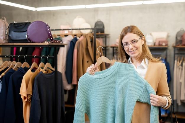 Feliz elegante mujer madura en abrigo y anteojos que le muestra un suéter de algodón azul mientras está de pie en el departamento de ropa