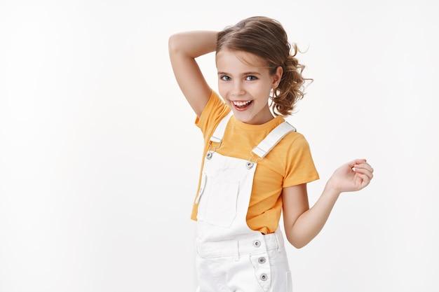 Feliz y elegante niña pequeña, peinando el cabello rubio para jugar con el patio de los amigos, sonriendo ampliamente, disfruta de las frescas vacaciones de verano, gira la cámara riendo sin preocupaciones, usa peto