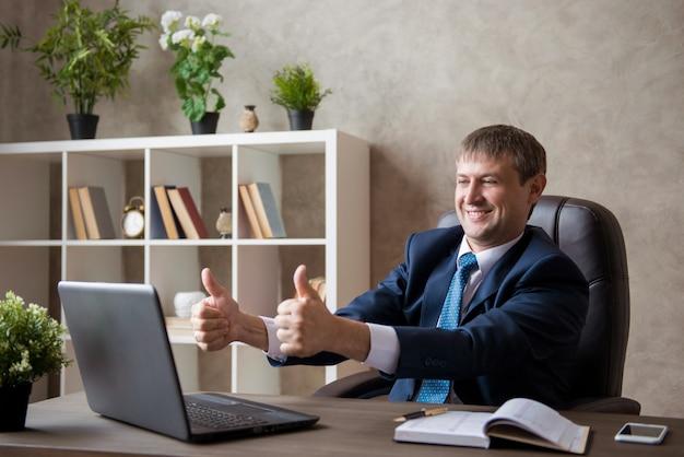 Feliz emocionada joven empresaria sentado en el lugar de trabajo que muestra la clase. negociaciones en línea.