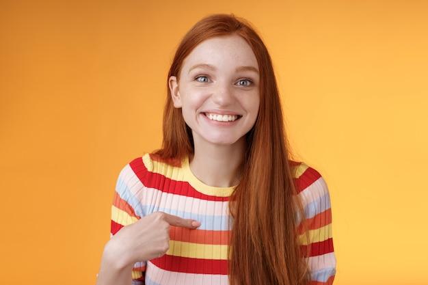 Feliz emocionada sonriente pelirroja elegida sonriente gratitud encantada apuntando con gusto a sí misma mirada sorpresa agradecida cámara consiguió trabajo, recibir beca permanente fondo naranja. copia espacio