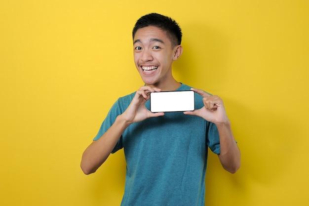 Feliz emocionado joven asiático mostrando la pantalla del teléfono blanco en la cámara, aislado sobre fondo amarillo
