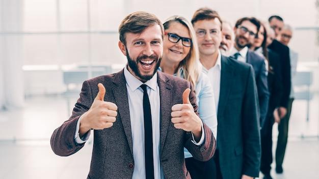 Feliz emprendedor de pie frente al equipo de negocios y dando un pulgar hacia arriba. el concepto de trabajo en equipo