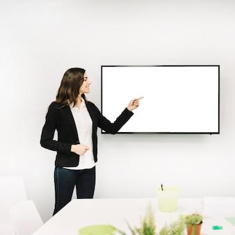 Feliz empresaria apuntando hacia la pantalla en blanco