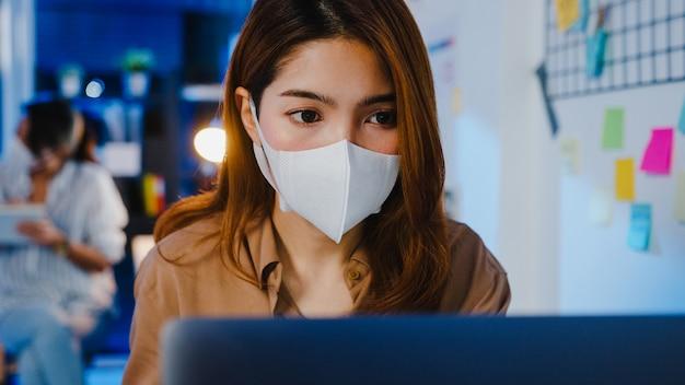 Feliz empresaria de asia con mascarilla médica para el distanciamiento social en una nueva situación normal para la prevención de virus mientras usa la computadora portátil en el trabajo en la noche de la oficina.
