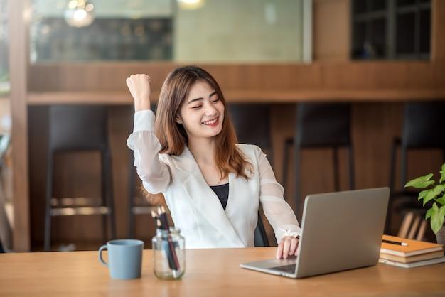 Feliz empresaria asiática celebrar el éxito con el brazo levantado frente a la computadora portátil en la oficina