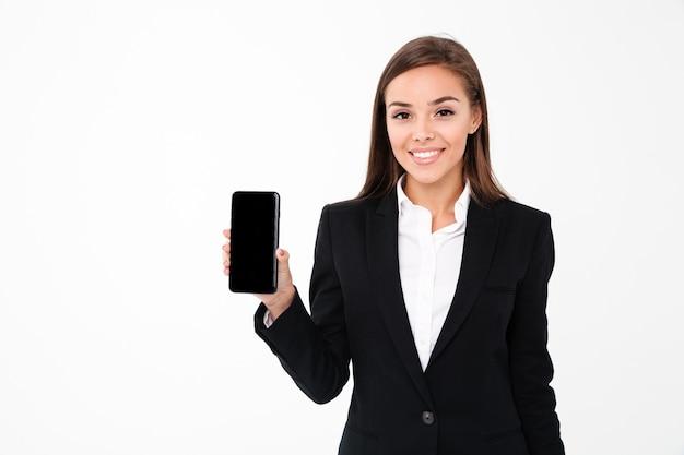 Feliz empresaria bonita que muestra la pantalla del teléfono móvil