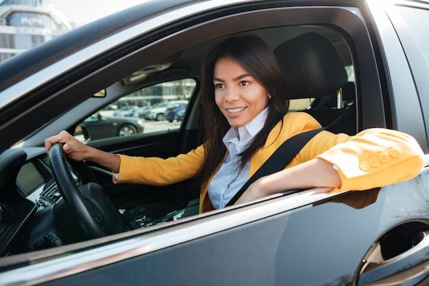 Feliz empresaria conduciendo su auto nuevo
